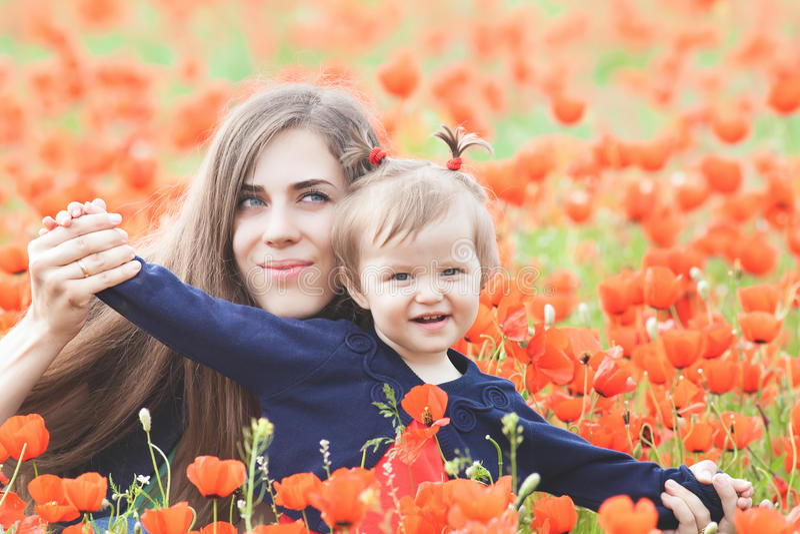 Moder med det roliga barnet som är utomhus- på vallmoblommafältet royaltyfria bilder