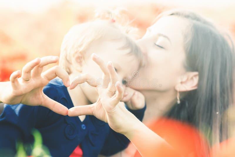 Moder med det roliga barnet som är utomhus- på vallmoblommafältet arkivbilder