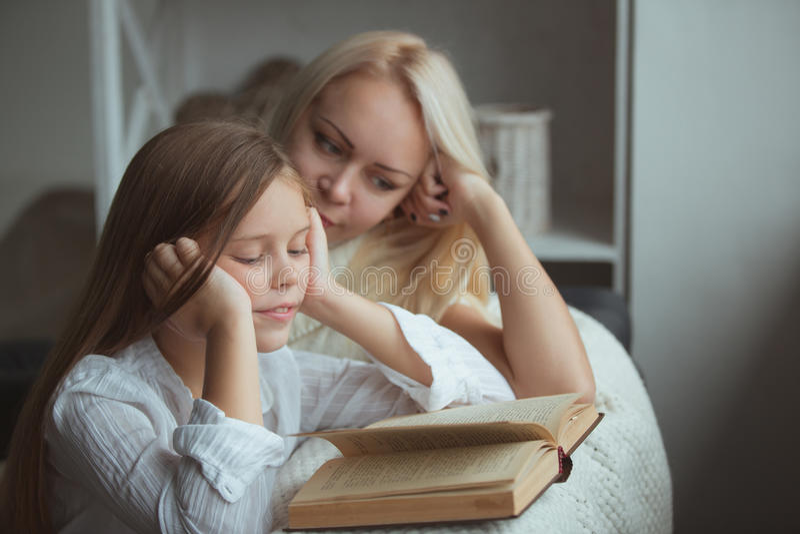 Moder med dotteravläsningsboken arkivfoton