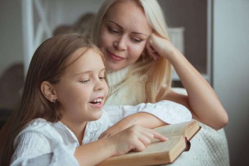 Moder med dotteravläsningsboken royaltyfri bild