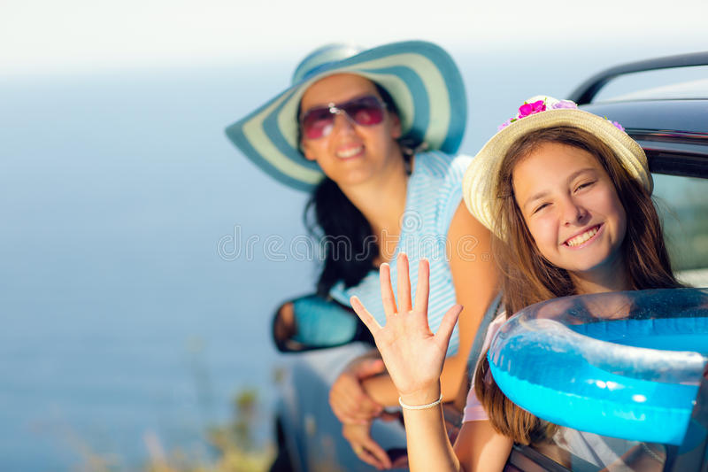 Moder med dotterlopp med bilen på havssemester arkivbild