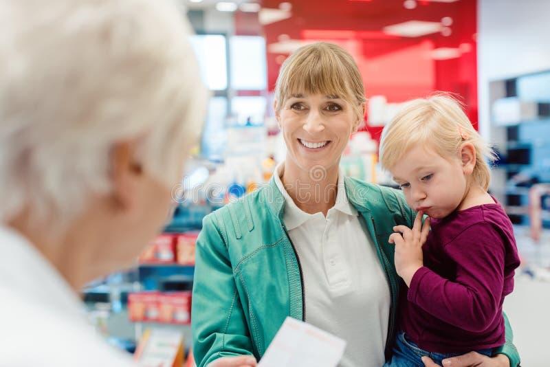 Moder med dottern i apotek på räknaren arkivfoton