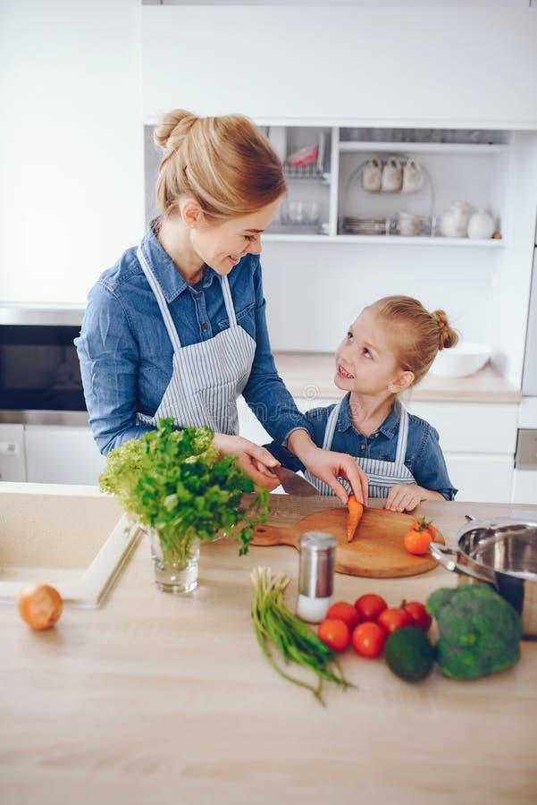 Moder med dottern i köket royaltyfria bilder