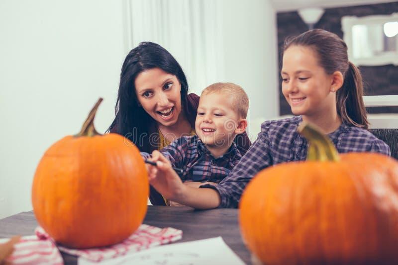 Moder med dottern och sonen som skapar stor orange pumpa royaltyfri fotografi
