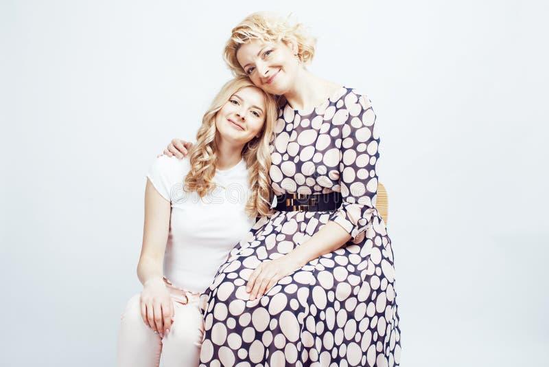 Moder med dottern som poserar tillsammans lyckligt le som isoleras på vit bakgrund med copyspace, livsstilfolkbegrepp royaltyfria bilder