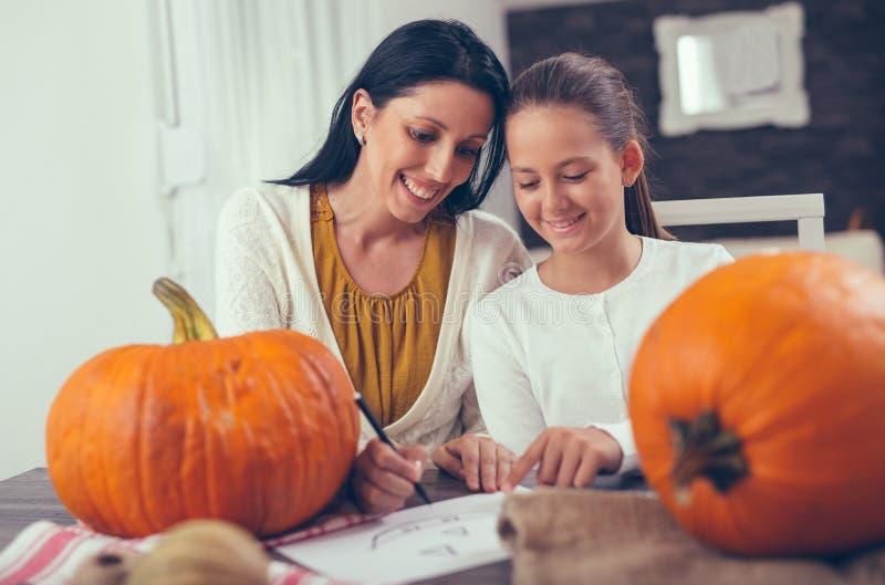 Moder med dottern som skapar stor orange pumpa arkivfoto
