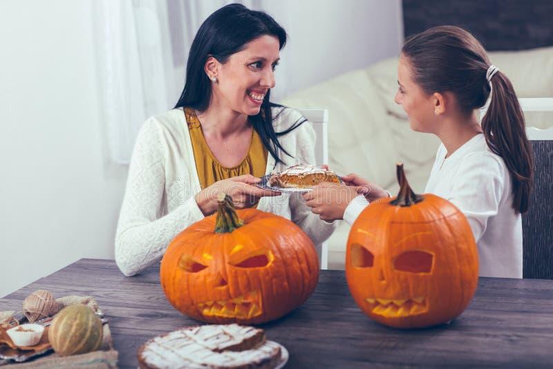 Moder med dottern som skapar stor orange pumpa för allhelgonaafton royaltyfria foton