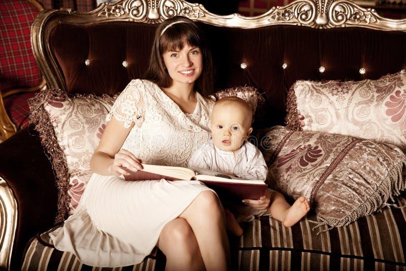 Moder med ett småbarn i den inre läsningen en boktogethe fotografering för bildbyråer