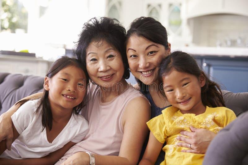 Moder med farmodern och sondöttrar som kopplar av på soffan arkivfoton