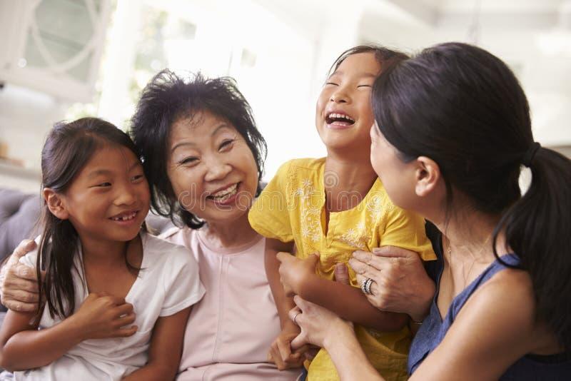 Moder med farmodern och sondöttrar som kopplar av på soffan arkivbild