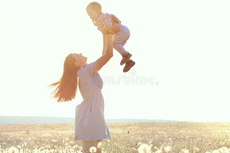 Moder med hennes barn i solljus arkivbild