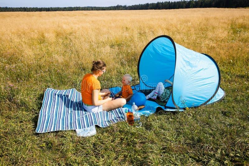 Moder med hennes barn och att ha en picknick royaltyfri fotografi