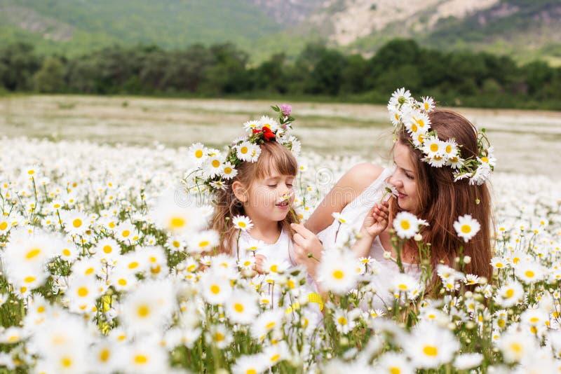 Moder med hennes barn som spelar i kamomillfält royaltyfria foton