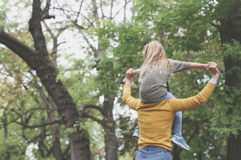 Moder med hennes dotter som spelar i natur Från baksida arkivfoto