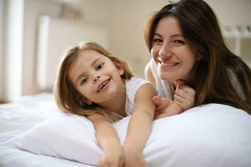 Moder med hennes gulliga lilla dotter som ligger på säng royaltyfri fotografi
