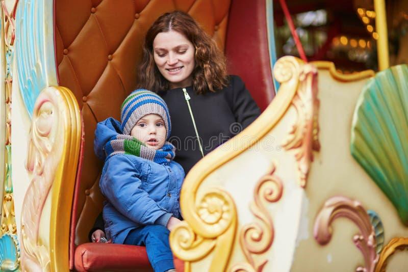 Moder med hennes lilla son på karusell i Paris arkivfoton
