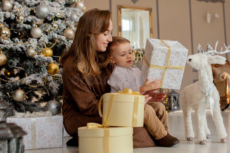 Moder med hennes lilla son som öppnar en julgåva i hemtrevlig vardagsrum Familjtid på ferier royaltyfria bilder