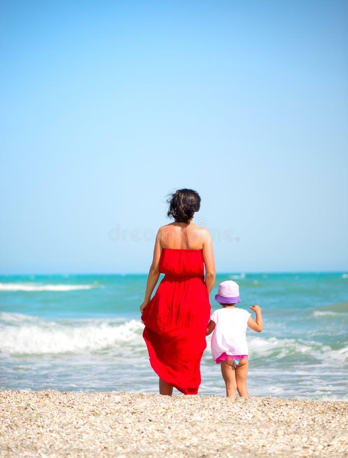 Moder med hennes liten flicka som g?r p? kusten royaltyfria bilder