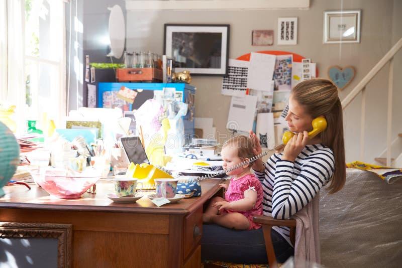 Moder med kontoret för små och medelstora företag för dotter det rinnande hemifrån arkivbilder