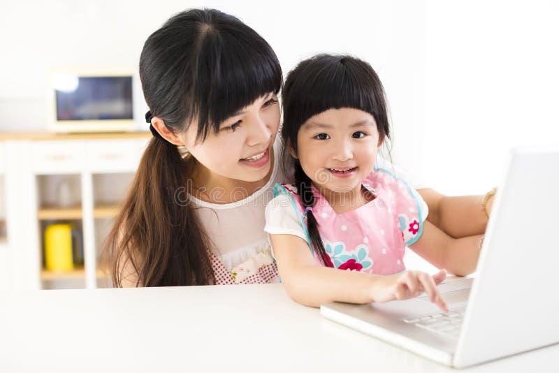 Moder med lilla flickan som använder bärbara datorn i köket royaltyfria bilder