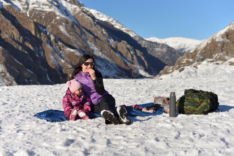 Moder med lite dottern i vinter på en picknick i bergen arkivfoto