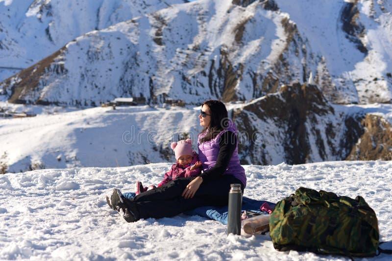 Moder med lite dottern i vinter på en picknick i bergen royaltyfria foton