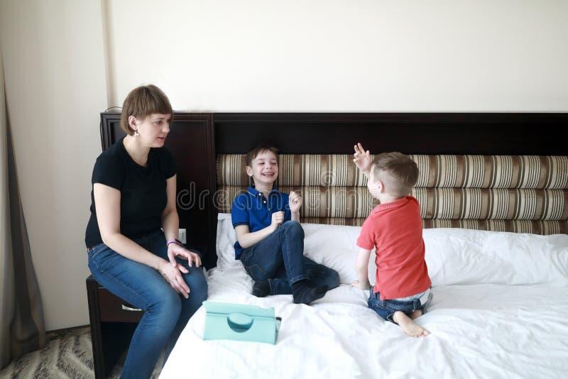 Moder med söner på säng arkivfoto
