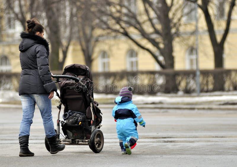 Moder med sittvagnen som går nära liten son royaltyfria bilder