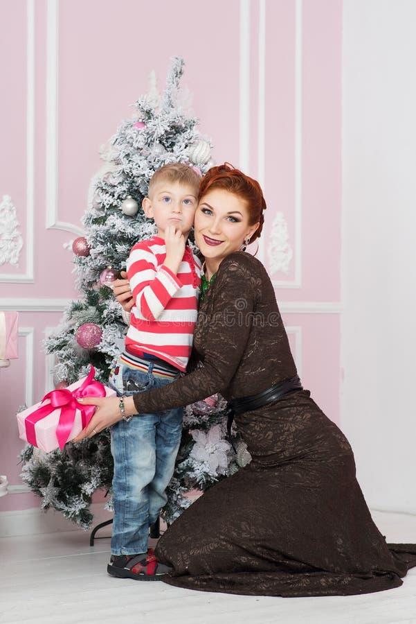 Moder med sonen nära granträd med gåvan nytt år för jul royaltyfria bilder
