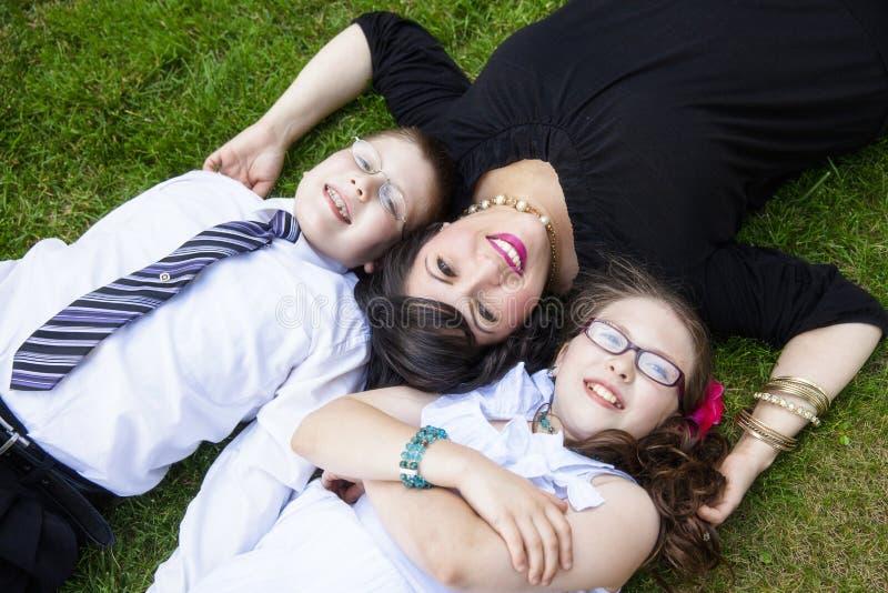 Moder med sonen och dottern som lägger i gräs arkivfoton