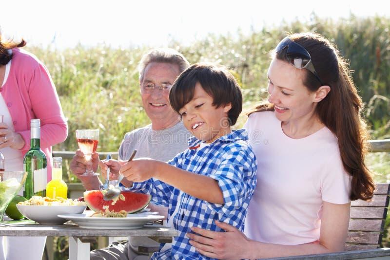 Moder med sonen och farfadern som tycker om den utomhus- grillfesten arkivfoto