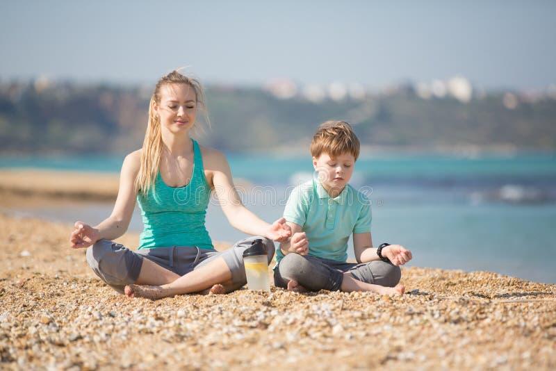 Moder med sonen som övar på stranden arkivfoto