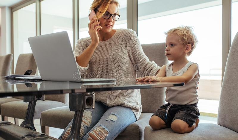 Moder med sonen som hemifrån arbetar arkivfoto