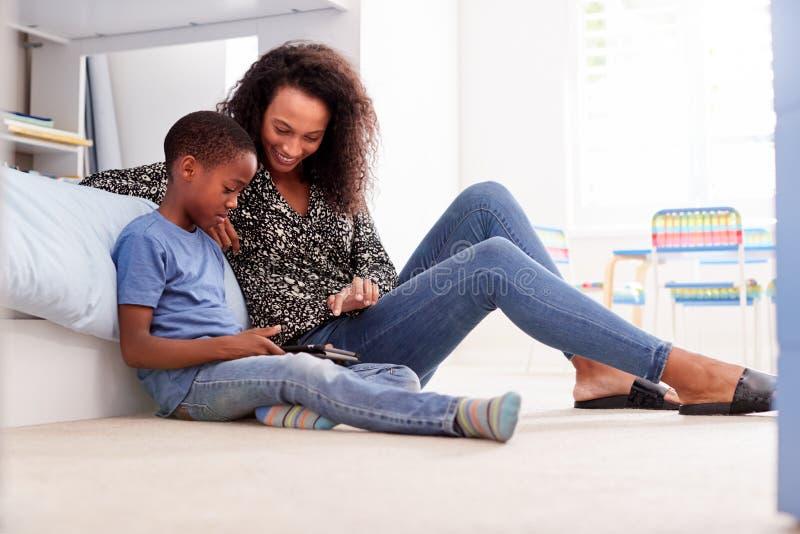 Moder med sonen som sitter på säng i det Childs sovrummet genom att använda den Digital minnestavlan tillsammans arkivbild