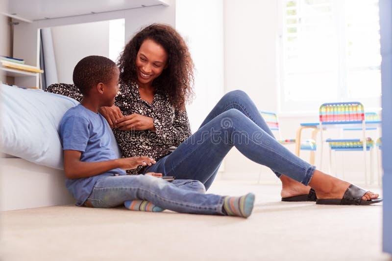 Moder med sonen som sitter på säng i det Childs sovrummet genom att använda den Digital minnestavlan tillsammans royaltyfria bilder