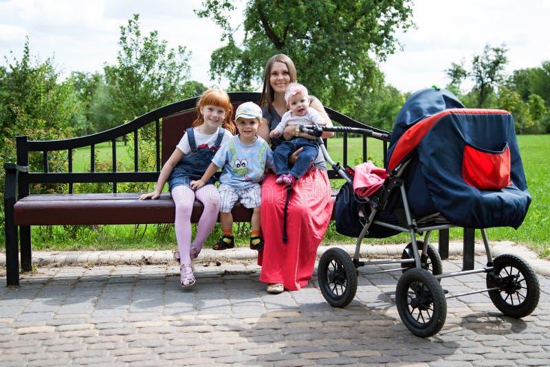Moder med tre barn arkivbild