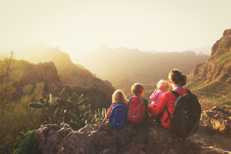 Moder med tre ungar som fotvandrar i berg royaltyfri foto