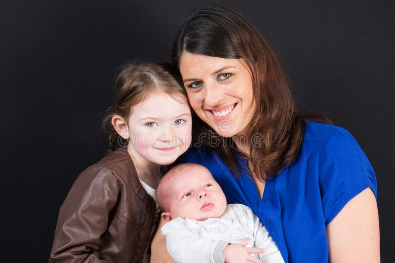 Moder med två barn på svart, lycklig le familj inom sondotter och singelmum arkivbild