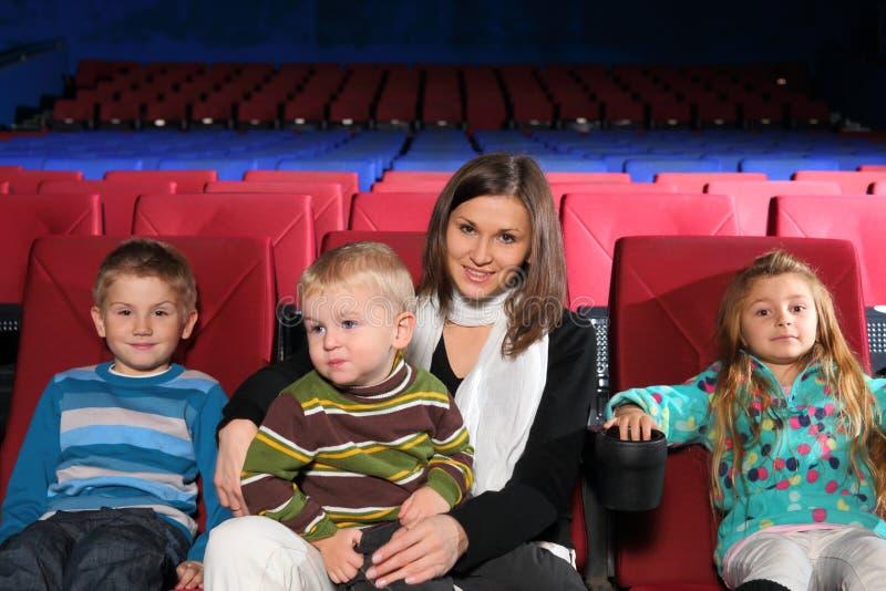 Moder med två söner och dottern i bion fotografering för bildbyråer
