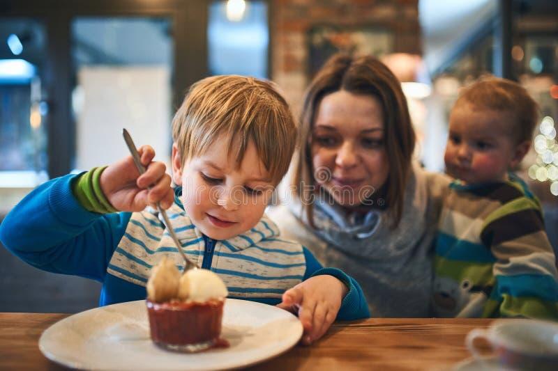 Moder med två ungar i väntande på beställning för kafé royaltyfri bild