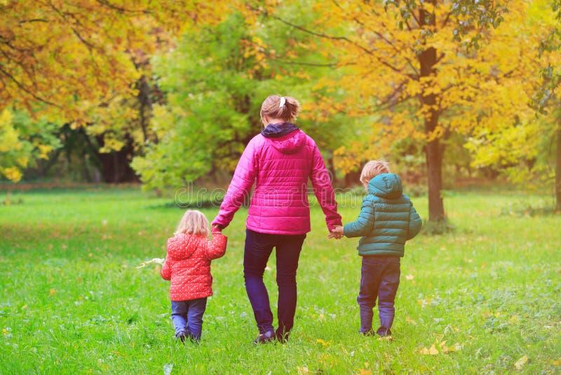 Moder med två ungar som går i höstnedgång royaltyfri foto