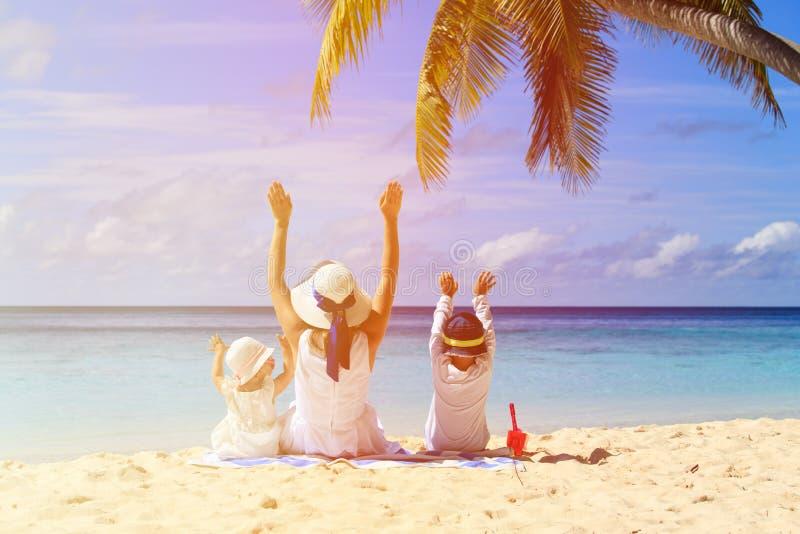 Moder med två ungehänder upp på stranden royaltyfria bilder