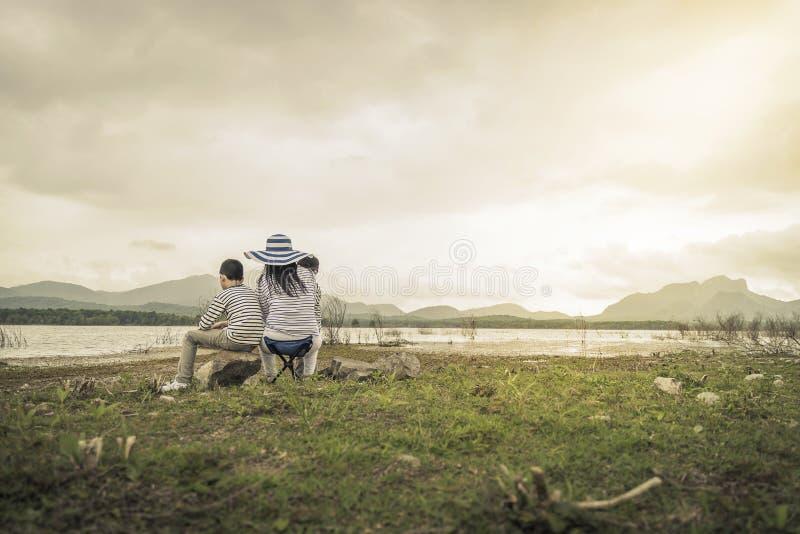 Moder med unga döttrar och sonen på picknick nära sjön royaltyfria bilder