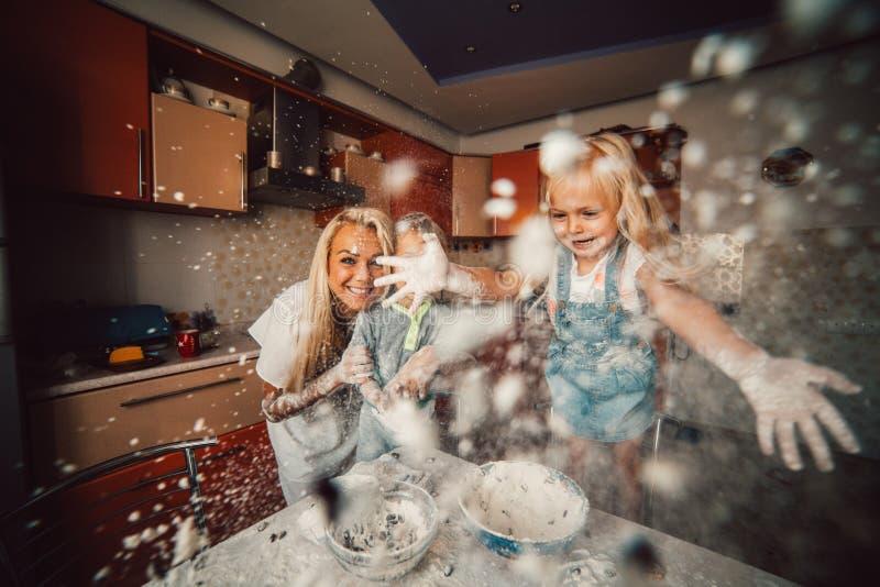 Moder med ungar på kök arkivbilder
