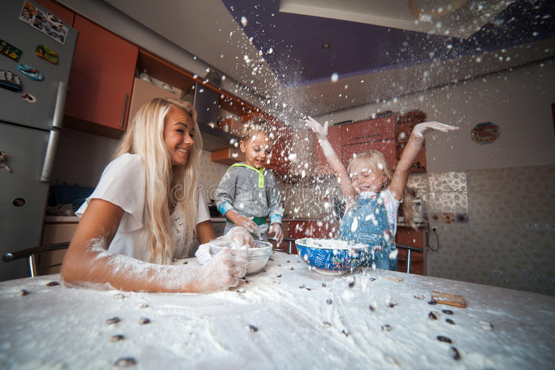 Moder med ungar på kök som kastar mjöl till överkanten arkivfoton