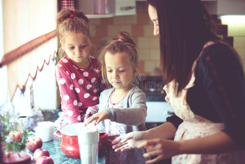 Moder med ungar på köket arkivbilder