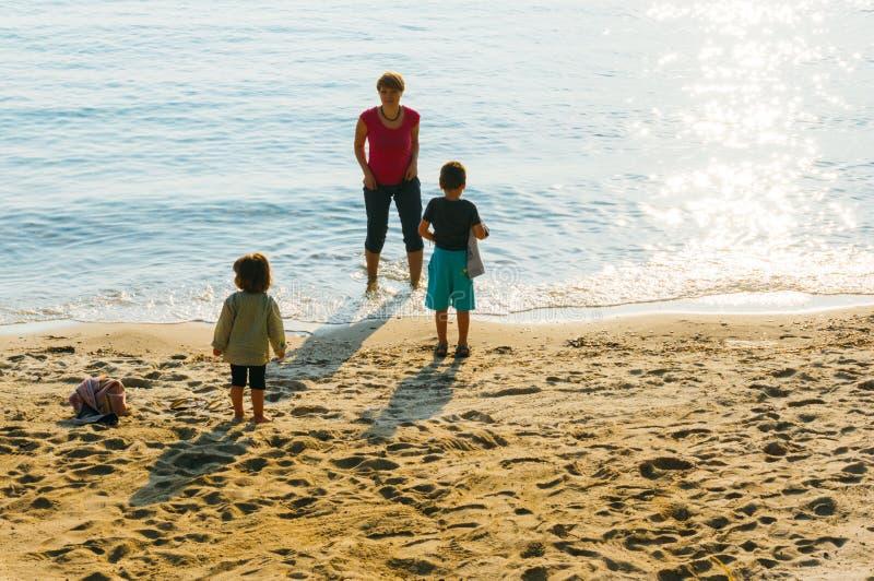 Moder med ungar på stranden arkivfoton