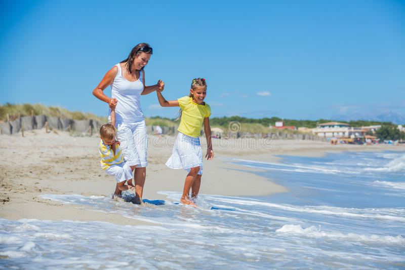 Moder med ungar på stranden fotografering för bildbyråer