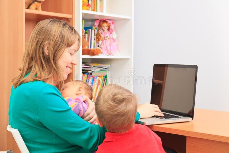 Moder med ungar som hemma arbetar på bärbara datorn royaltyfri bild