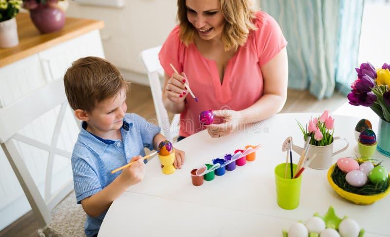 Moder med ungen som målar easter ägg arkivbild